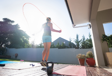 A woman jumps rope outside on her deck on a sunny day.