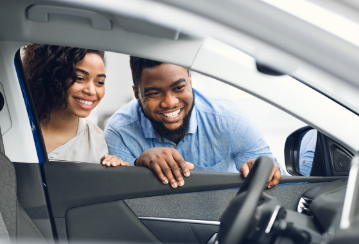 A smiling couple peer into a car through an open driver's side window while considering buying the car.