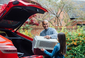 A daughter helps her father load a pet crate into the back of their car.