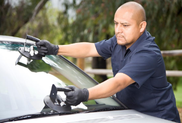 Man using suction cups to remove windshield