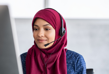 A woman wearing a headset smiles as she works at her computer.
