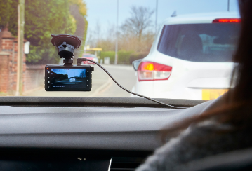 A dash cam installed on the windshield records the traffic in front of the car.
